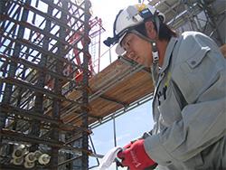 現場で鉄筋の配筋検査を行う当社技術者